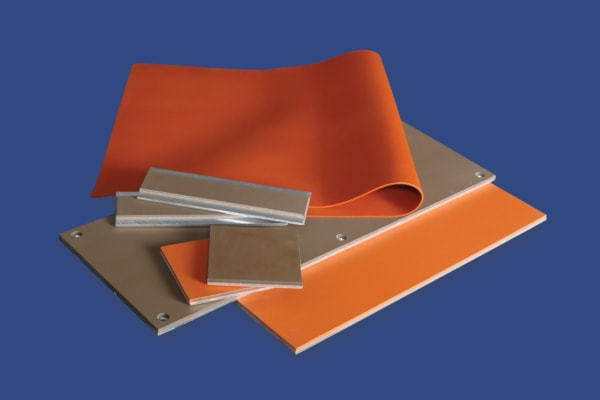 A color photo of both unbonded and silicone-to-metal bonded high temperature silicone rubber sheets.